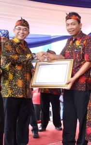Opik (Ketua TBM aiueo Komunitas Ngejah) menerima Piagam Penghargaan TBM Kreatif-Rekretaif dari Kemendikbud